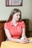 Het meisje in rode blouse zit in een restaurant bij een lijst met a stock fotografie