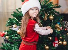 Het meisje in rode hoed verfraait een Kerstmisboom Stock Afbeeldingen