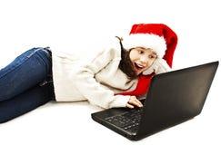 Het meisje in rode Kerstmanhoed kijkt geschokt wanneer het bekijken laptop computer Stock Foto