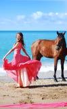 Het meisje in rode kleding danst op strand stock afbeeldingen