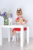 Het meisje in rode kleding zit bij lijst en wateren van de kop dol Royalty-vrije Stock Foto