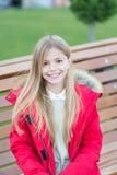Het meisje in rode laag zit op bank in park Royalty-vrije Stock Afbeeldingen