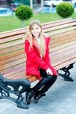 Het meisje in rode laag zit op bank in park Royalty-vrije Stock Fotografie