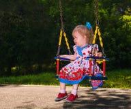 Het meisje rollen-op een schommeling in het park Stock Afbeeldingen