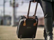 Het meisje rolt een zwarte koffer op het spoorwegplatform, close-up stock foto