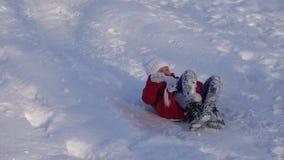 Het meisje rolt heuvel in ar in sneeuw naar beneden meisjesspelen in de winter in het park Langzame Motie stock video