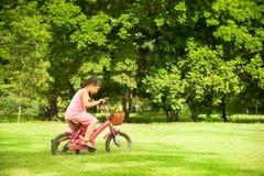Het meisje in roze kleding berijdt haar fiets op het gras Royalty-vrije Stock Afbeelding