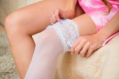 Het meisje in roze zijdepeignoir zet op witte kousen Stock Foto