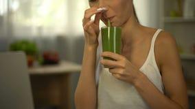 Het meisje ruikt groene smoothie, voelt afschuw, smaakloos maar gezonde voeding, close-up stock videobeelden
