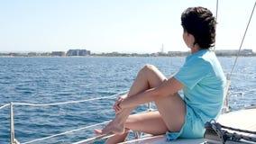 Het meisje rust aan boord van een jacht of een boot op een zonnige dag op de open zee Een vrouw zit op het dek en onderzoekt stock footage