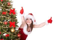 Het meisje in santahoed en de boom met twee beduimelen omhoog Stock Foto's