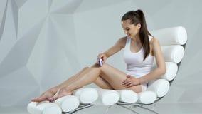 Het meisje scheert haar benen met een depilator, wordt haar huid vlot en zijdeachtig stock footage