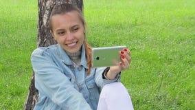 Het meisje schiet zich in het park Selfie stock videobeelden