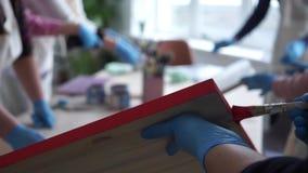 Het meisje schildert een houten beeld Gloved Handen Rode verf Art Studio stock footage