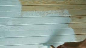 Het meisje schildert een houten raad met witte verf, hoogste mening stock videobeelden