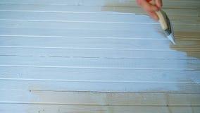 Het meisje schildert een houten raad met witte verf in langzame motie, hoogste mening stock video