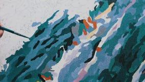 Het meisje schildert een mooi beeld met acrylverven op canvas Kleuring-antistress voor volwassenen stock videobeelden
