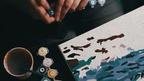 Het meisje schildert een mooi beeld met blauwe acrylverven op canvas Kleuring-antistress voor volwassenen stock videobeelden