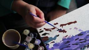 Het meisje schildert een mooi beeld met blauwe acrylverven op canvas Kleuring-antistress voor volwassenen stock video