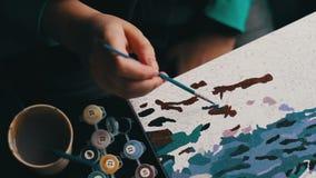 Het meisje schildert een mooi beeld met blauwe acrylverven op canvas Kleuring-antistress voor volwassenen stock footage