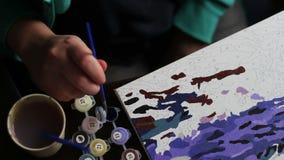 Het meisje schildert een mooi beeld met blauwe acrylverven op canvas Kleuring-antistress voor volwassenen tijd-tijdspanne stock video