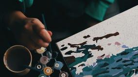 Het meisje schildert een mooi beeld met blauwe acrylverven op canvas Kleuring-antistress voor volwassenen tijd-tijdspanne stock videobeelden