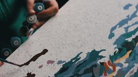 Het meisje schildert een mooi beeld met Bruine acrylverven op canvas Kleuring-antistress voor volwassenen stock video