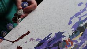 Het meisje schildert een mooi beeld met Bruine acrylverven op canvas Kleuring-antistress voor volwassenen stock videobeelden