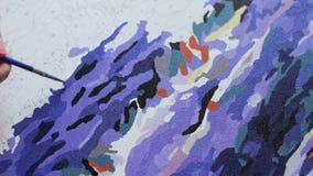 Het meisje schildert een mooi beeld met lilac acrylverven op canvas Kleuring-antistress voor volwassenen tijd-tijdspanne stock footage