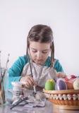 Het meisje schildert eieren Stock Afbeeldingen