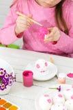 Het meisje schildert eieren met een borstel royalty-vrije stock fotografie