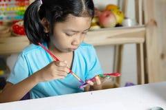 Het meisje schildert kleur op vinger royalty-vrije stock afbeelding