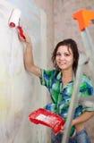 Het meisje schildert muur met rol stock afbeeldingen