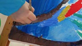 Het meisje schildert oliënbeeld met borstel stock videobeelden