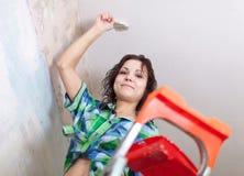 Het meisje schildert plafond stock foto