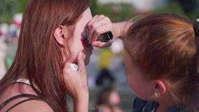 Het meisje schildert Russische vlag op haar tante ` s cheeck alvorens het spel begint stock footage