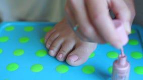 Het meisje schildert spijkers op haar juiste voet stock video