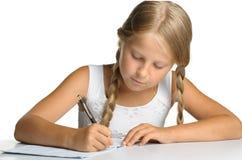 Het meisje schrijft aan schrijven-boeken Royalty-vrije Stock Foto