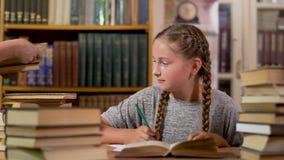 Het meisje schrijft bij een lijst in de bibliotheek stock videobeelden