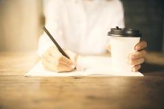 Het meisje schrijft in een agenda met kop van koffie Stock Fotografie
