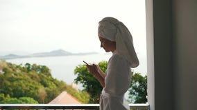 Het meisje schrijft een bericht op een smartphone op vakantie stock footage