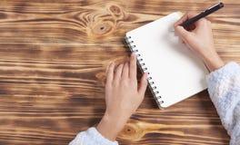 Het meisje schrijft in een notitieboekje stock fotografie