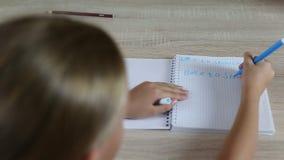 Het meisje schrijft terug naar school in notitieboekje met spellingfout Jonge meisjeszitting door bureaulijst Het witte meisje sc stock footage