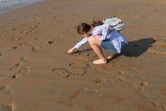 Het meisje schrijft het woord 'Liefde 'en een symbool van hart op het zand bij zonsondergang Voetafdrukken op het overzeese zand stock foto's