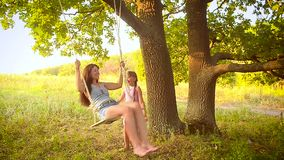 Het meisje schudt haar mamma op schommeling in park, slingert op boom stock videobeelden