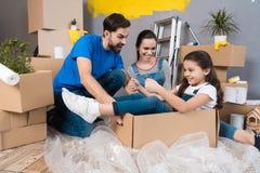Het meisje simuleert vlucht op vliegtuig, zittend in doos naast ouders Huisvernieuwing voor verkoop royalty-vrije stock fotografie