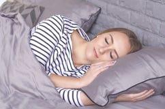 Het meisje slaapt in bed stock afbeeldingen