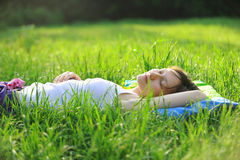 Het meisje slaapt in het gras Stock Foto's