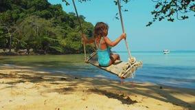 Het meisje slingert op houten schommeling op een zandig strand door de oceaan stock video