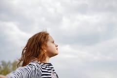Het meisje sloot haar ogen en ademhaling met verse blazende lucht stock afbeelding